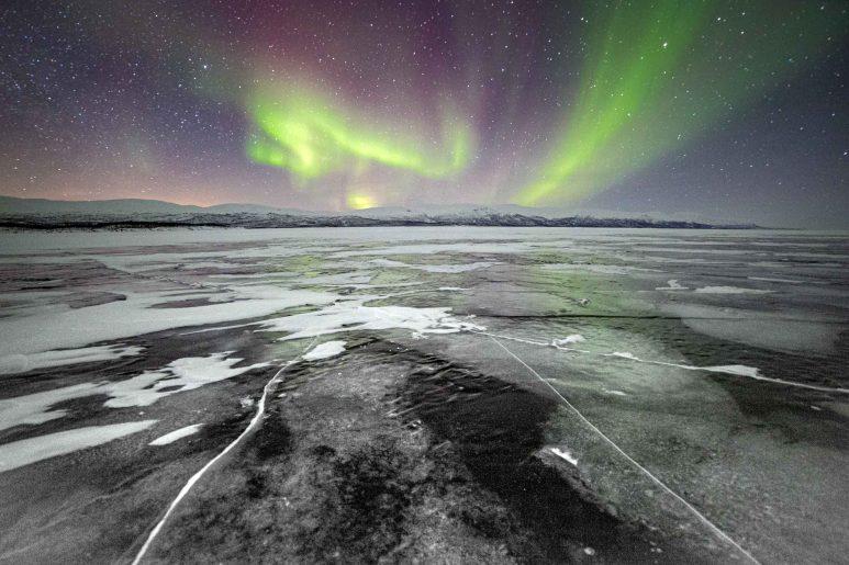 Black lake under aurora